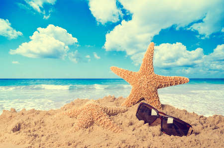Starfish on beach with sunglasses against a lovely summer sky - vintage feel photo