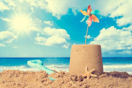 Sandcastle on sandy beach with pinwheel against a summer sky - vintage feel