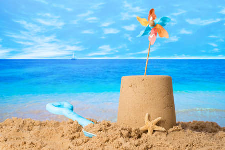 Sandcastle with windmill on summer beach Stock Photo
