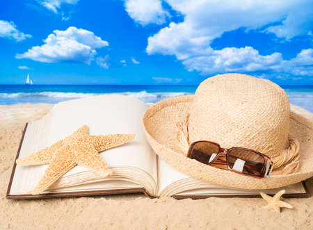 Straw hat with sunglasses and open book on sandy beach