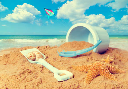 spade: Beach scene with bucket and spade against ocean background with kite flying Stock Photo