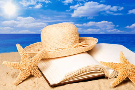 Straw sunhat lying on an open book on sandy beach in summer