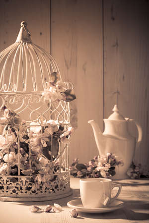 teatime: Afternoon tea with birdcage filled with apple blossom in background - vintage tone Stock Photo