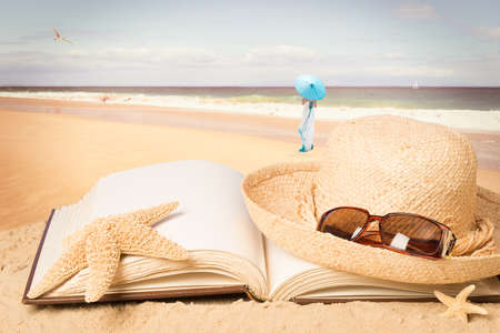 vacation: Straw hat and sunglasses lying on book overlooking the ocean
