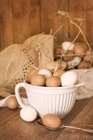 Eggs on spoon with straw hat and basket of eggs in background with vintage textured effect photo