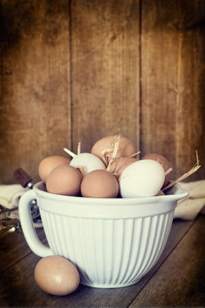 Fresh eggs in bowl with vintage textured effect photo