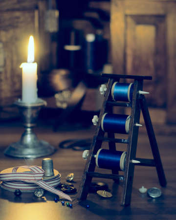 sewing box: Sewing by candlelight with antique cotton reels - vintage duo tone effect Stock Photo