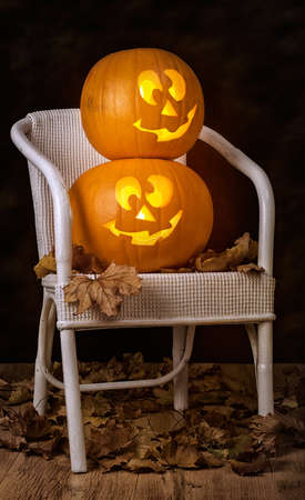 Brightly lit pumpkins sitting on chair surrounded by fallen leaves Stock Photo