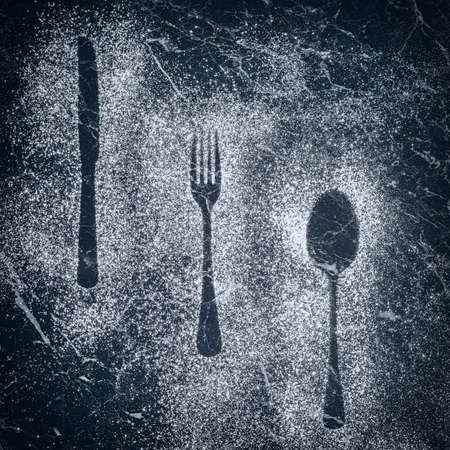 Outlines of knife, fork and spoon made with a dusting of icing sugar photo