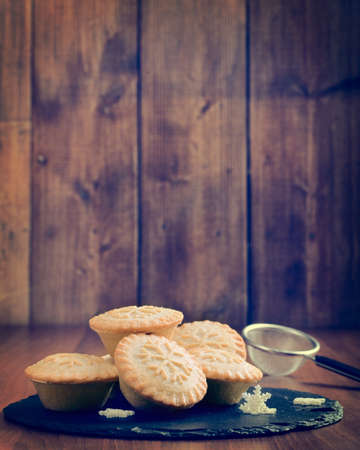 fayre: Mince pies on slate serving plate in rustic vintage setting Stock Photo