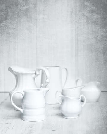 milk jugs: Collection of white jugs on rustic grungy background