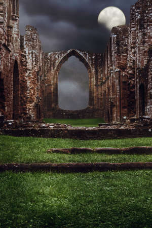 stone steps: Steps leading to the ruins of an abbey at night with dark brooding sky Stock Photo