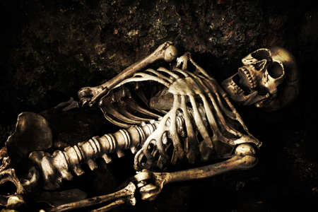 Skeleton lying in shallow grave at Halloween photo