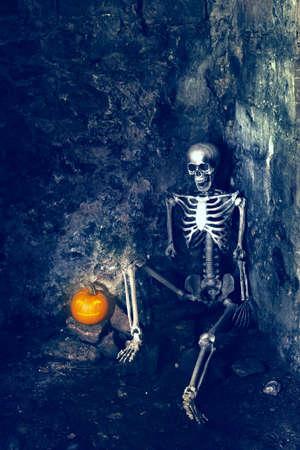 Skeleton with Jack O Lantern sitting in forgotten grave photo
