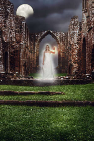 Ghost holding lamp haunting the steps of a ruined abbey photo