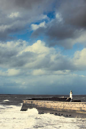 whitehaven: Waves crashing against the sea wall with lighthouse at Whitehaven, England, UK
