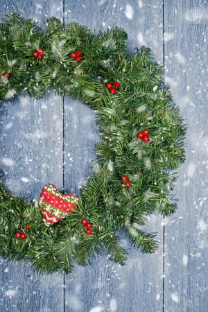 Christmas wreath hanging from rustic door with falling winter snow photo