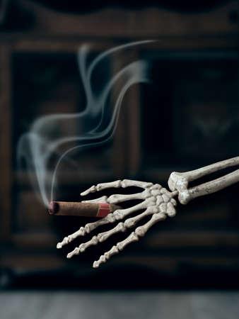 Smoking cigar in skeleton hand - representative of the hazard of smoking to health photo