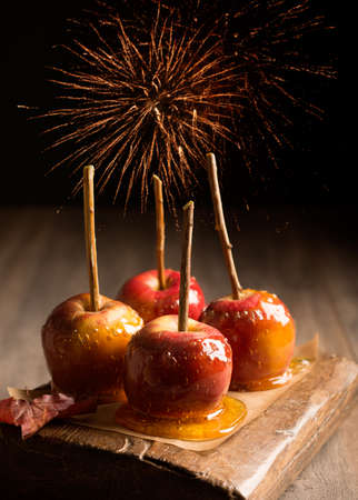 toffee: Group of toffee apples on rustic wooden board with fireworks in the background