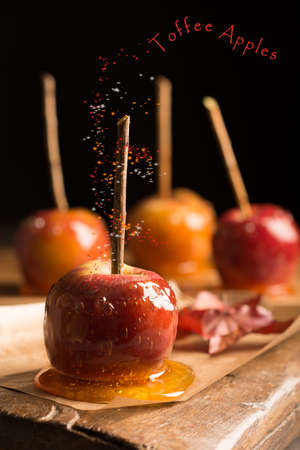 toffee: Group of toffee apples on rustic wooden board