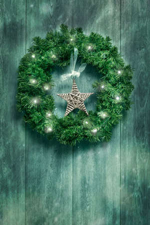 Christmas garland with twinkling lights hanging on rustic door photo
