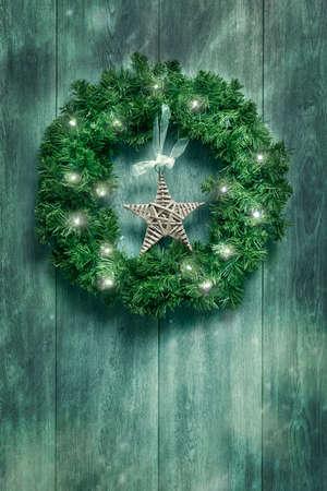 Ghirlanda di Natale con le luci scintillanti appesi sulla porta rustica Archivio Fotografico