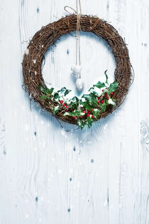 Rustic Christmas garland decorated with holly and berries hanging on white door photo
