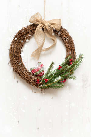 Winter garland hanging from door with falling snow photo