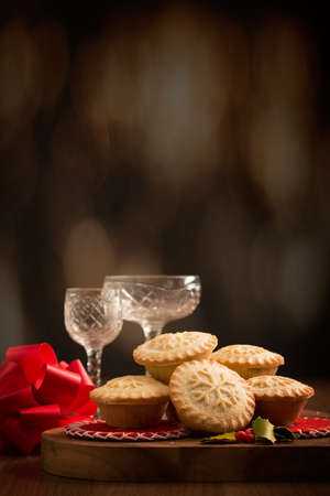 Homemade Christmas mince pies with festive background