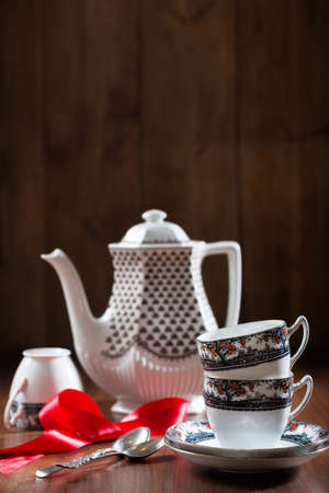 Teacups and saucers with teapot in rustic setting photo