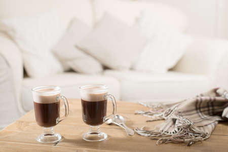 coffees: Two Irish coffees on table with winter scarf Stock Photo
