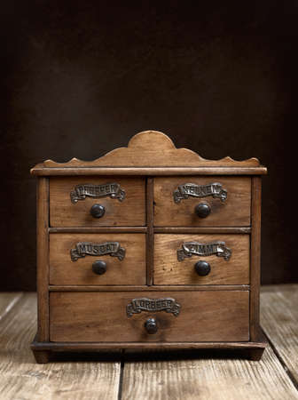 chest of drawers: Vintage spice cabinet on rustic wooden table Stock Photo