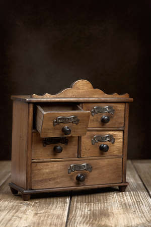 Spice cabinet on rustic wooden table with open drawer