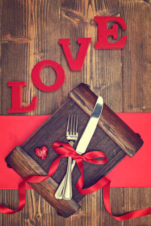 Cutlery tied with red ribbon for Valentine menu table setting photo