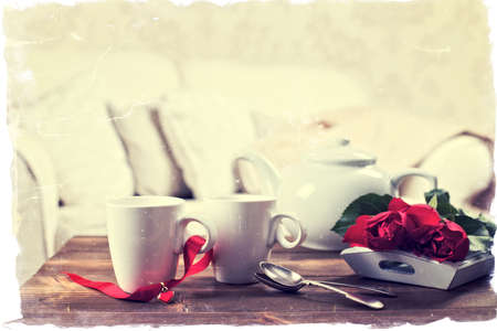 old photograph: Tea cups with roses for Valentines Day - vintage tone effect old photograph style