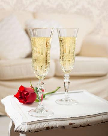 Twee glazen champagne met een rode roos