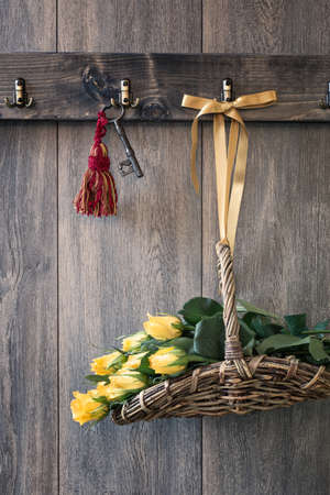 garden key: Basket of freshly picked yellow roses hanging on shed door