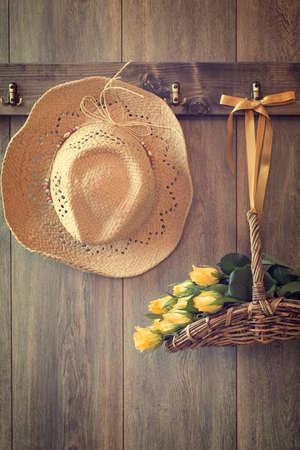 Strohhut und Korb mit Rosen hängen auf Holztür