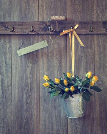 Eimer mit gelben Rosen an Wand mit leeren Zeichen für Ihren Text gefüllt Standard-Bild