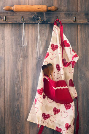 Apron hanging on hook in kitchen with utensils - vintage tone effect