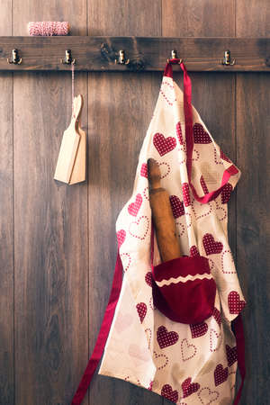 pat: Cooks apron with rolling pin and butter pats hanging on hooks in the kitchen - vintage tone effect Stock Photo