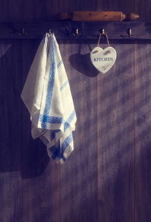 Kitchen teatowels hanging on wall with sunrays filtering through  photo
