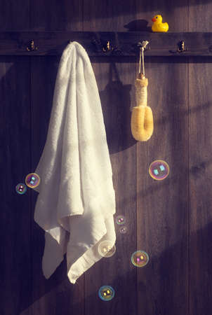 White towel with loofah hanging on wall with floating bubbles and sunlight filtering through - vintage tone effect photo