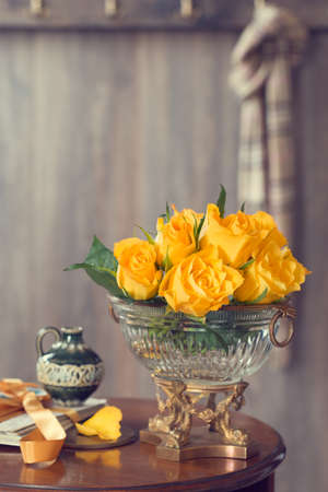 antique vase: Country house reception hall with table adorned with yellow roses in an antique vase