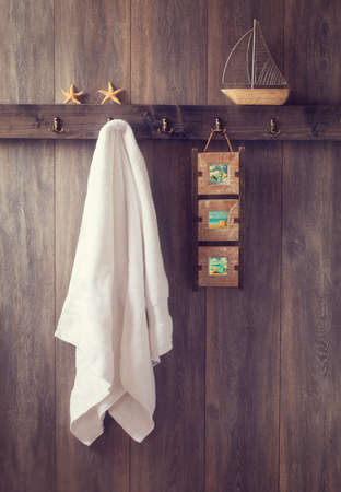 Bathroom wall with hanging towel and photo frame and toy boat