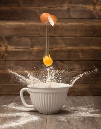 An egg being cracked into a bowl of flour