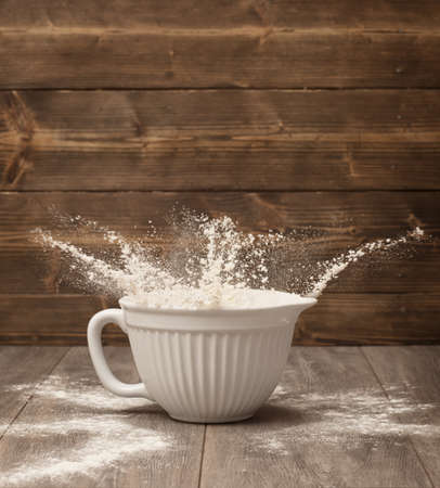 worktop: Flour flying out of a white mixing bowl in the kitchen