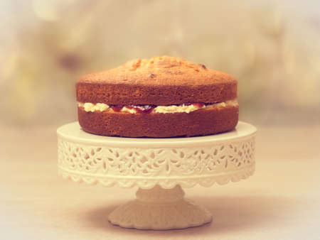 Victoria sponge cake filled with jam and buttercream - antique vintage tone effect added Stock Photo