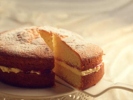 잼과 버터 크림 필링을 드러내는 빅토리아 스폰지 케이크를 슬라이스