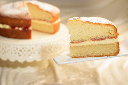 pound cake: A slice of Victoria sponge cake with cut cake in the background